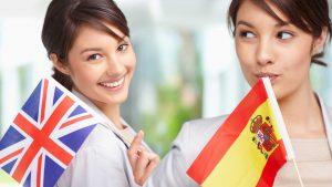 Zwei junge Frauen. Die links stehende hält ein Fähnchen Großbritanniens in der Hand die rechts stehende ein Fähnchen Spaniens.