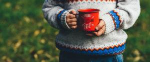 """Bild eines Kindes mit Tasse auf der steht """"Young, wild and free""""."""