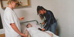 Altenpflegerinnen während praktischer Übungen am Pflegebett mit Pflegepuppe.