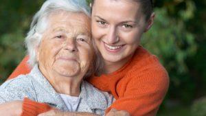 In einem Park umarmt eine Altenpflegerin eine Seniorin. Beide schauen in die Kamera.