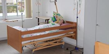 Praxisraum für die Ausbildung zum/zur Pflegehelfer/-in mit Pflegebett und Pflegepuppe am mediCampus - gesundheitsfachberufe.